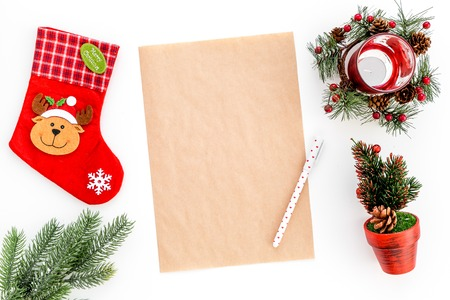 New Year or Christmas mockup. Template for letter to Santa, list of plans and goals for New Year, wishlist near fir branches, Christmas socks on white background top view