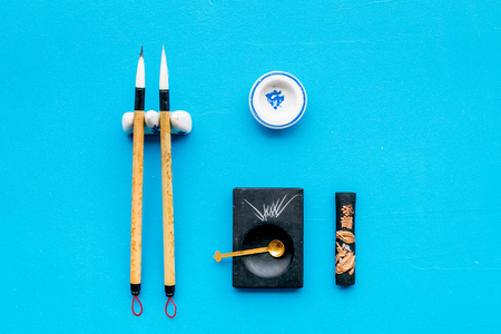 Accessories for chinese or japanese calligraphy. Special writting pen, ink on blue background top view copy space