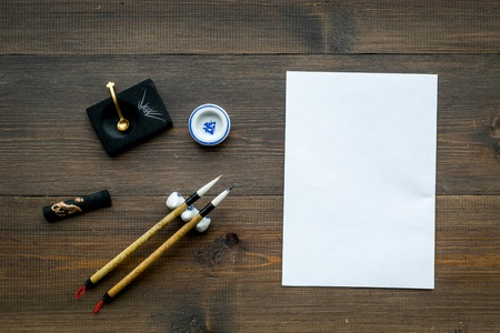 Lesson of calligraphy concept. White blank sheet for lettering near writing accessories on dark wooden background top view mockup 스톡 콘텐츠