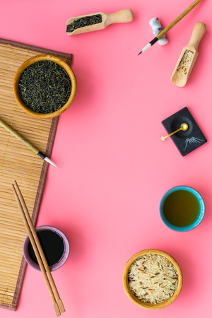 Chinese traditional symbols concept. Tea, rice, hieroglyph love, bamboo table mat, chopsticks, soy sause on pink background top view frame space for text Archivio Fotografico