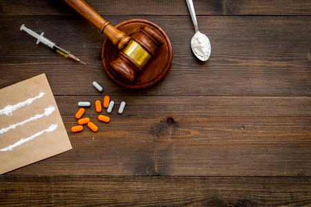 Adicción a las drogas, arresto por drogas. Píldoras, cuchara con polvo, jeringa sobre fondo de madera oscura, vista superior, espacio de copia