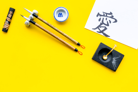 Chinese or japanese calligraphy concept. Hieroglyph love near traditional written accessories on yellow background top view space for text 스톡 콘텐츠