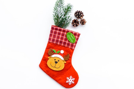 Christmas decoration. Traditional festive socks with spruce branch and pine cones on white background top view copy space