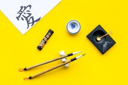 Chinese or japanese calligraphy concept. Hieroglyph love near traditional written accessories on yellow background top view