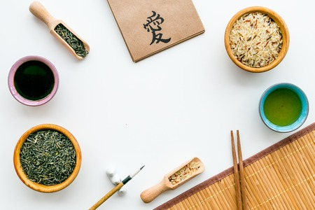 Chinese traditional symbols concept. Tea, rice, hieroglyph love, bamboo table mat, chopsticks, soy sause on white background top view frame copy space Stock Photo