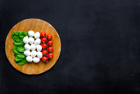 Italian flag made of mozzarella cheese, cherry tomatoes, green basil on wooden cutting board on black background top view copy space Reklamní fotografie - 112902101