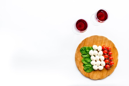 Italian cuisine, food concept. Italian flag made of mozzarella, tomatoes, basil on wooden cutting board near glass of red wine on white background top view copy space