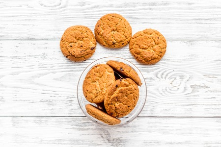 Homemade oatmeal cookies in glass bowl on white woden background top view copy space