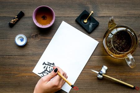 Calligraphy. Hand writes hieroglyph love on white paper on dark wooden background top view