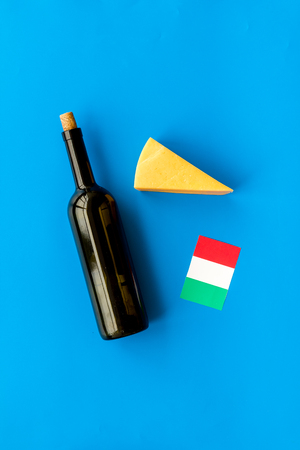 Gastronomical tourism. Italian food symbols. Italian flag, cheese parmesan and bottle of red wine on blue background top view copy space