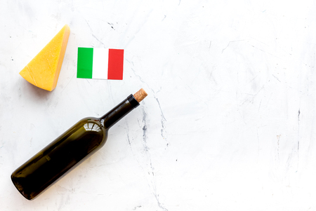 Gastronomical tourism. Italian food symbols. Italian flag, cheese parmesan and bottle of red wine on white background top view space for text Reklamní fotografie - 112902207