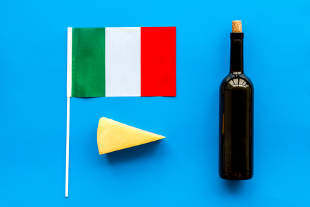Gastronomical tourism. Italian food symbols. Italian flag, cheese parmesan and bottle of red wine on blue background top view Reklamní fotografie