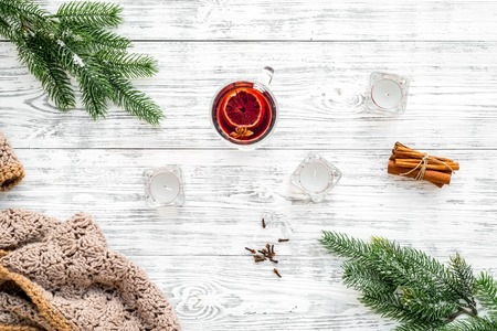 Hot beverage for warm winter evening. Mulled wine near fir branches, wool blanket, candles on white wooden background top view Stock Photo