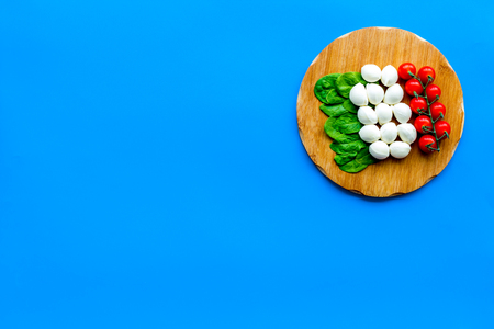 Italian flag made of mozzarella cheese, cherry tomatoes, green basil on wooden cutting board on blue background top view copy space Stock Photo