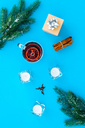 Winter beverage for New Year or Christmas Eve. Mulled wine near fir branches, candles, cinnamon on blue background top view