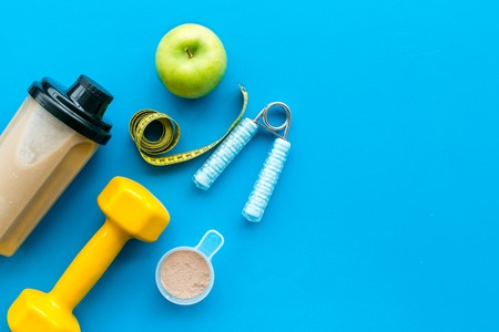 sport diet with protein nutrition and fitness equipment on blue background top view mock up