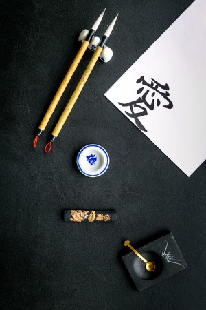 Chinese or japanese calligraphy concept. Hieroglyph love near traditional written accessories on black background top view. 스톡 콘텐츠