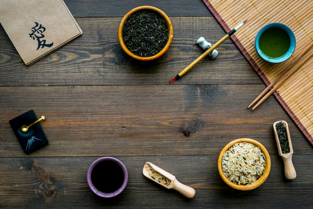 Chinese traditional symbols concept. Tea, rice, hieroglyph love, bamboo table mat, chopsticks, soy sause on dark wooden background top view frame. Stockfoto - 112959326