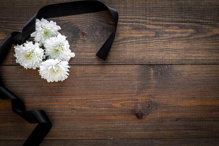 Funeral symbols. White flower near black ribbon on dark wooden background top view. Zdjęcie Seryjne