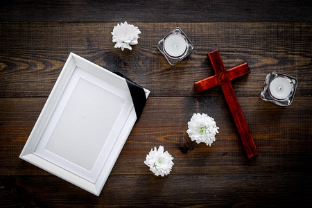 Funeral. Mockup of portrait of the deceased, of dead person. Frame with black ribbon near flowers, candles and cross on dark wooden background top view.