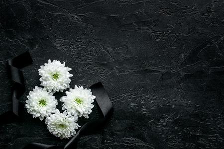 Begräbnissymbole. Weiße Blume nahe schwarzem Band auf Draufsicht des schwarzen Hintergrundes.