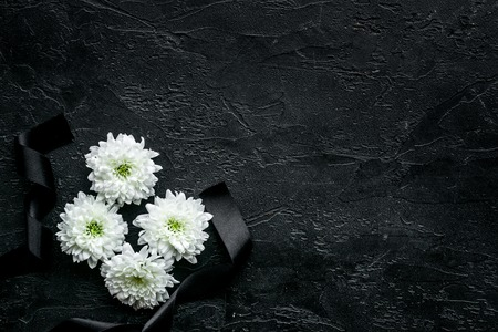 Funeral symbols. White flower near black ribbon on black background top view.