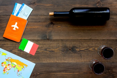 Gastronomical tourism. Italian food symbols. Passport and tickets near italian flag, bottle of red wine, map of the world on dark wooden background top view.
