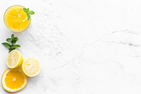 Orange juice and citrus cocktails. Juice in glass near cut orange and lemon, crushed ice, green mint on white stone background top view.