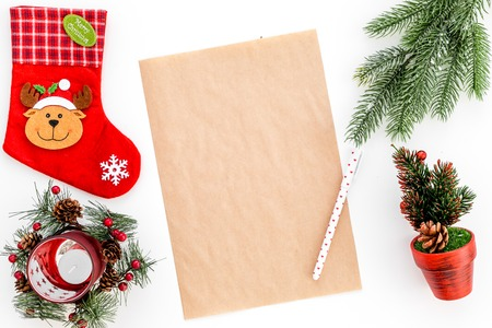 New Year or Christmas mockup. Template for letter to Santa, list of plans and goals for New Year, wishlist near fir branches, Christmas socks on white background top view.