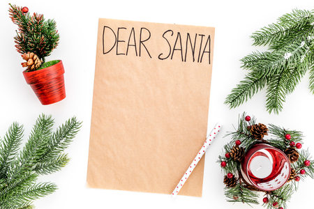 Letter to Santa Claus template. Mockup on craft paper with text Dear Santa near New Year decoration like fir branches, candle, festive tree on white background top view.