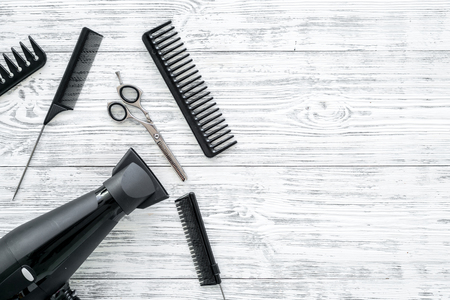 Set of professional hairdresser tools with combs on gray wooden background top view mock-up