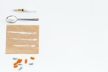 Take drugs, drugs addiction concept. White powder like heroine or cocaine, drug tracks pills, spoon, syringe on white background top view. Stockfoto