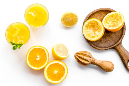Squeeze fresh oranges with juicer. Orange juice in glass near half cut oranges on white background top view. 版權商用圖片