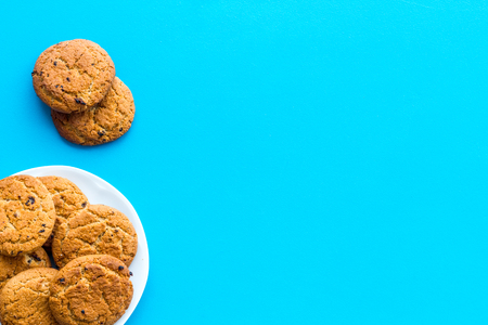 Homemade oatmeal cookies on white plate on blue background top view.