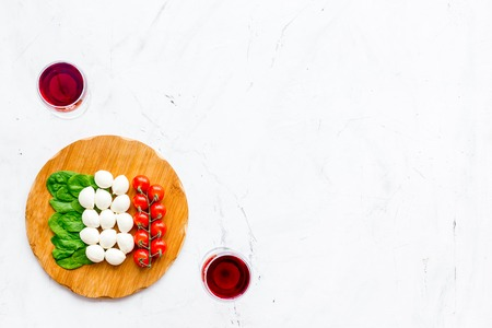 Italian cuisine, food concept. Italian flag made of mozzarella, tomatoes, basil on wooden cutting board near glass of red wine on white stone background top view. Reklamní fotografie