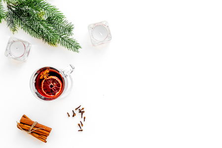 Winter beverage for New Year or Christmas Eve. Mulled wine near fir branches, candles, cinnamon on white wooden background top view. Stock Photo