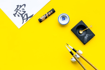 Chinese or japanese calligraphy concept. Hieroglyph love near traditional written accessories on yellow background top view. Imagens