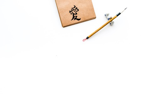 Chinese traditional calligraphy concept. Asian hieroglyph love in craft paper notebook near special writting pen on white background top view. Stok Fotoğraf