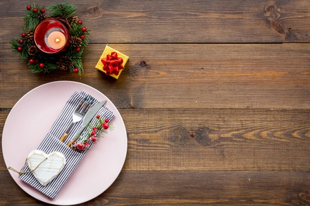 Christmas table setting with gift box and fir tree on wooden background top view mockup