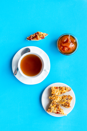 Dessert for evening tea. Cup of tea, fresh homemade cookies on blue background top view