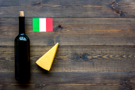 Gastronomical tourism. Italian food symbols. Italian flag, cheese parmesan and bottle of red wine on dark wooden background top view copy space
