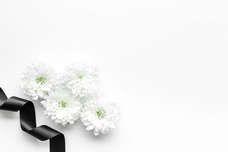 Begräbnissymbole. Weiße Blume in der Nähe von schwarzem Band auf weißem Hintergrund Draufsicht Kopie Raum
