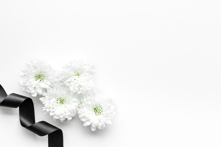 Funeral symbols. White flower near black ribbon on white background top view copy space Stockfoto