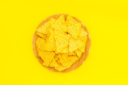 Mexican snack. Make nachos. Crispy nachos on wooden cutting board on yellow background top view. Stock Photo