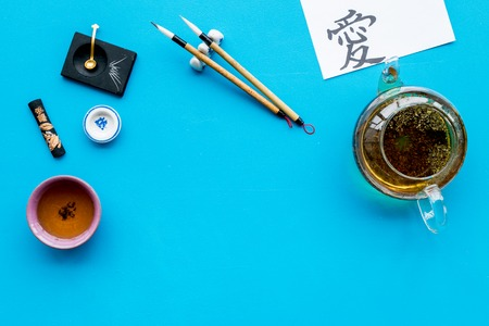 Lesson of calligraphy concept. Paper with hieroglyph love near writing accessories, teapot and cup of tea on blue background top view. Stok Fotoğraf