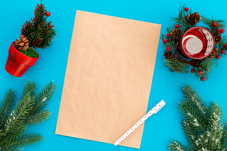 New Year or Christmas mockup. Template for letter to Santa, list of plans and goals for New Year, wishlist near fir branches, candle, festive tree on blue background top view.