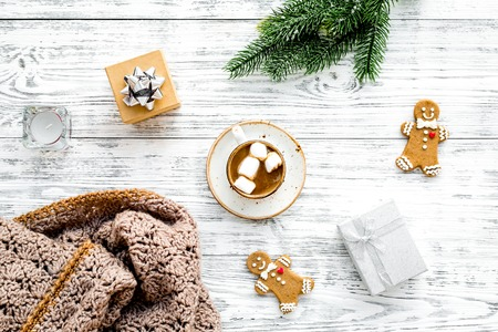 Romantic winter composition with hot drink. New Year or Christmas Eve. Cocoa with marshmallow, gift box, gingerbread man, wool blanket, fir branches on white wooden background top view.