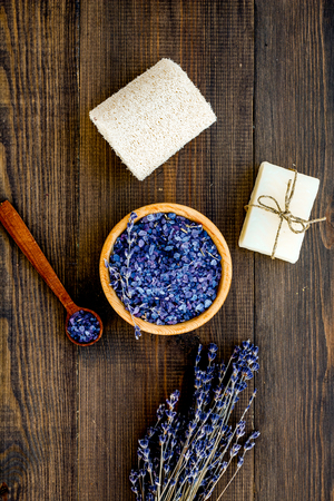 Spa set with lavender spa salt. Purple spa salt near dry lavender branches and washcloth on dark wooden background top view.