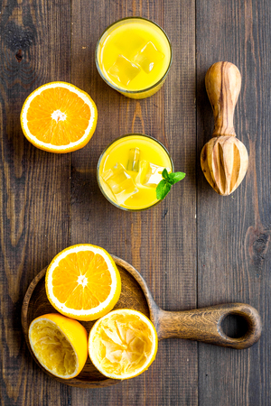 Squeeze fresh oranges with juicer. Orange juice in glass near half cut oranges on dark wooden background top view. Banco de Imagens