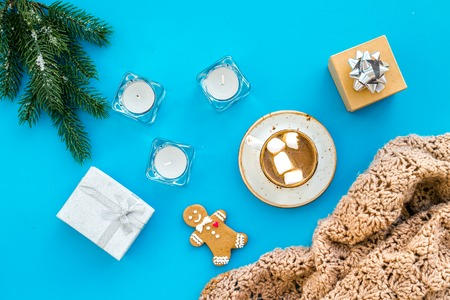 Romantic winter composition with hot drink. New Year or Christmas Eve. Cocoa with marshmallow, gift box, gingerbread man, wool blanket, fir branches on blue background top view